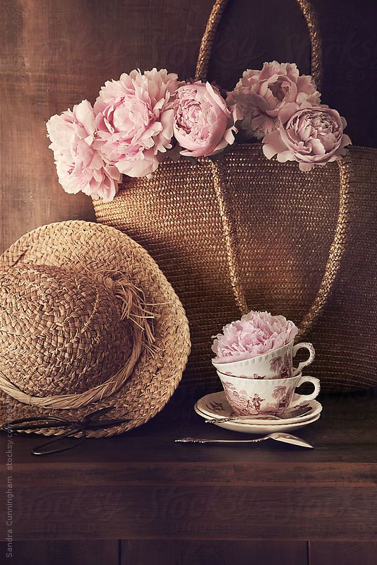 Freshly cut peonies with wicker hat and bag by Sandra Cunningham
