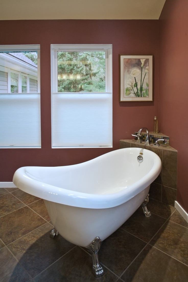 We love this modern version of a claw foot bathtub. Click through to see  the rest of this space, including a beautiful multi-colored glass tile wall!