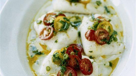 Häll lite olivolja i en ugnssäker form. Lägg i fisken och ringla över ytterligare lite olivolja. Krydda med salt och peppar. Baka i ugn på 100° varmluft ca 20 minuter beroende på fiskens tjocklek. Om du inte har varmluftsugn, öka temperaturen 25° och förläng tiden till ca 30–35 minuter. Blanda tomater med salladslök och persilja. Tillsätt olivolja och smaka av med citronsaft, salt och peppar.