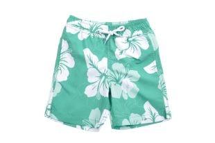 Traje de baño tipo Boardshort para bebe niño en color verde y con flores grandes en blanco y verde claro. Cintura elastizada y bolsillo en la parte de atrás.