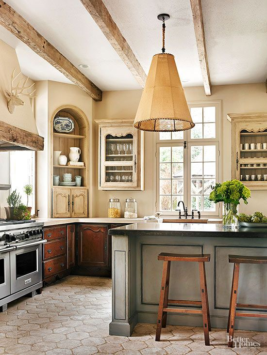The earliest kitchens came together slowly, with cupboards, workstations, and fixtures added at different times. These homeowners achieved a similar built-over-time look in their new kitchen by opting for different weathered cabinetry finishes, a mix of cabinet styles, and two types of countertops. Rustic ceiling beams, foot-worn stone floors, and antiqued plaster walls complete the old-world composition.