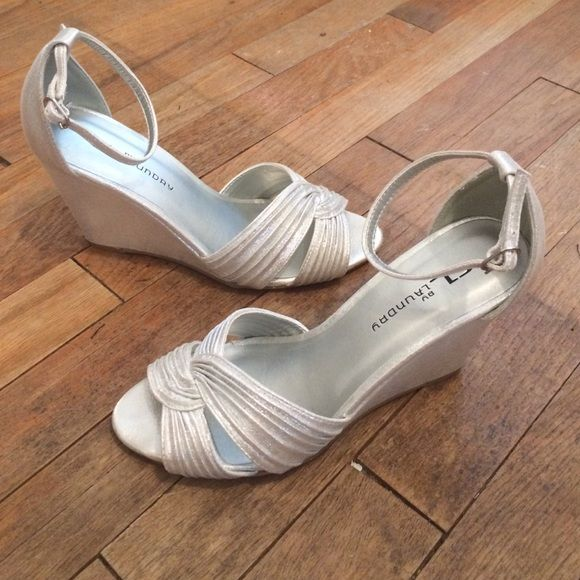 Silver wedge heel Silver wedge with ankle strap. Worn once in a wedding. Perfect shoe for inside or outside event and so comfortable. Ankle strap is adjustable. Wedge is about 3.5 inches. They fit true to size. Chinese Laundry Shoes Wedges