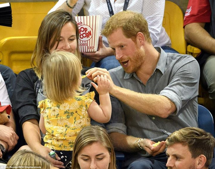 On Wednesday, Harry doted on two-year-old Emily in the stands at the Sitting Volleyball. He is seen feeding her popcorn