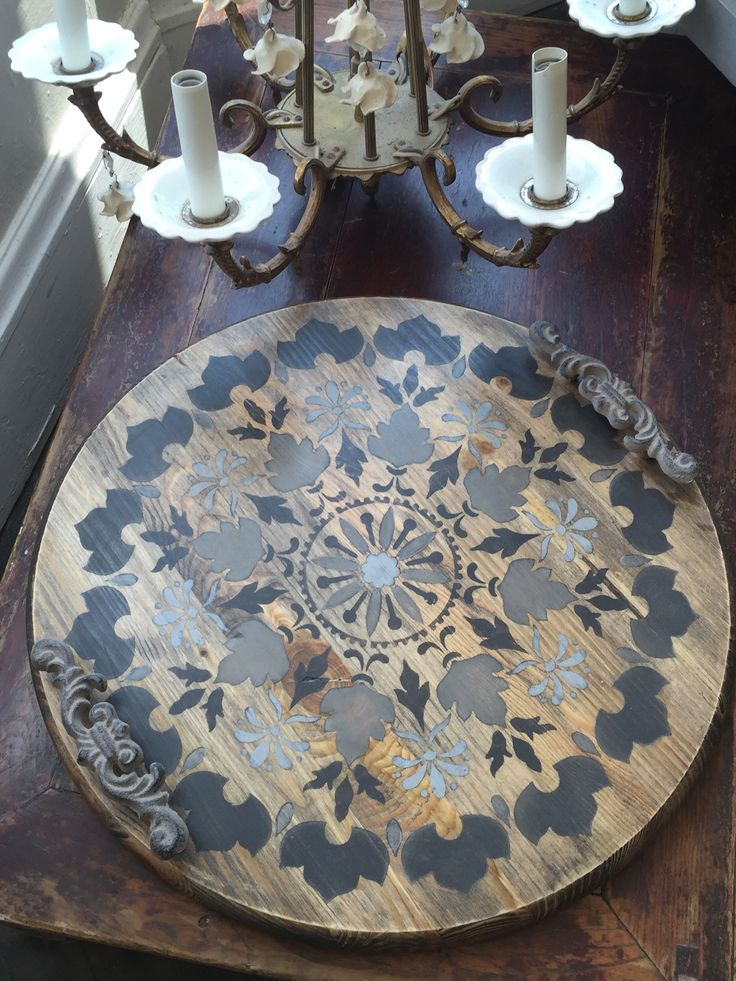 We took a round unfinished table top and waxed using Black Chalk Paint® wax then stenciled with Royal Design Stencil. Attached a couple of drawer pulls and voila.