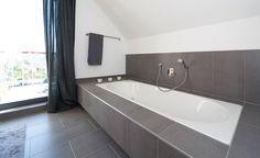 Badewanne mit breit gefliester Ablage unter Dachschräge