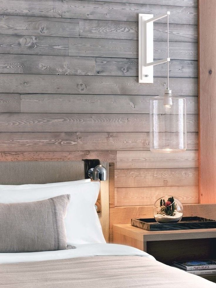Clear sconces on each side of the bed create a modern and luxurious beach decor…