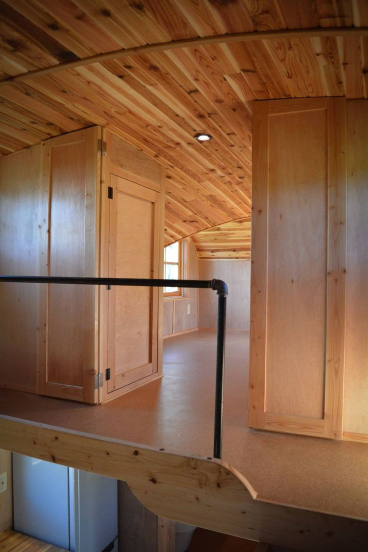 Sleeping loft in a tiny house with wood ceiling, wood closets, and metal railing.