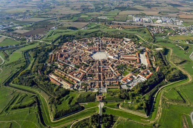 """Kuzey İtalya'nın Slovenya sınırına yakın bir alanda Palmanova adında bir yerleşim yeri bulunuyor. Palmanova'yı özel kılan ise yerleşim planı. """"Yıldız kale"""" adı verilen bir sur sistemi ile korunan bölge, rönesansta ideal bir yerleşim alanı olarak kurulmuş."""