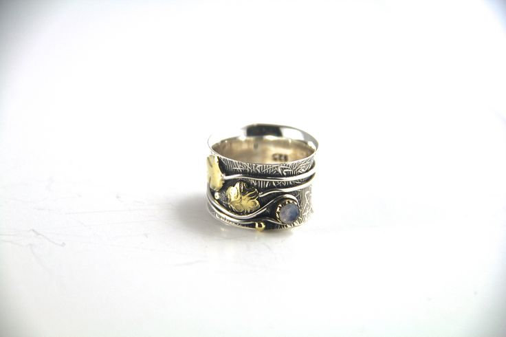 This is a really stunning ring with layers of detail. The design was inspired by a rainforest. The base of the ring has lovely bamboo-like leaves etched into it. The ring has been oxidised to produce a nice black-ish tint to it, so the bamboo-leaves have a great background setting. Vines with gold-plated leaves are then soldered around the ring, giving this ring a really unique look.The final detail is the small gemstone set in the vines. Just gorgeous. #statementring #handmade #silverring…