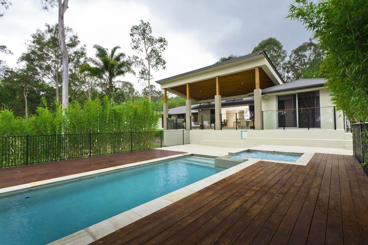 Modern lap pool with square hot tub surrounded by a wood deck  at a tropical home.