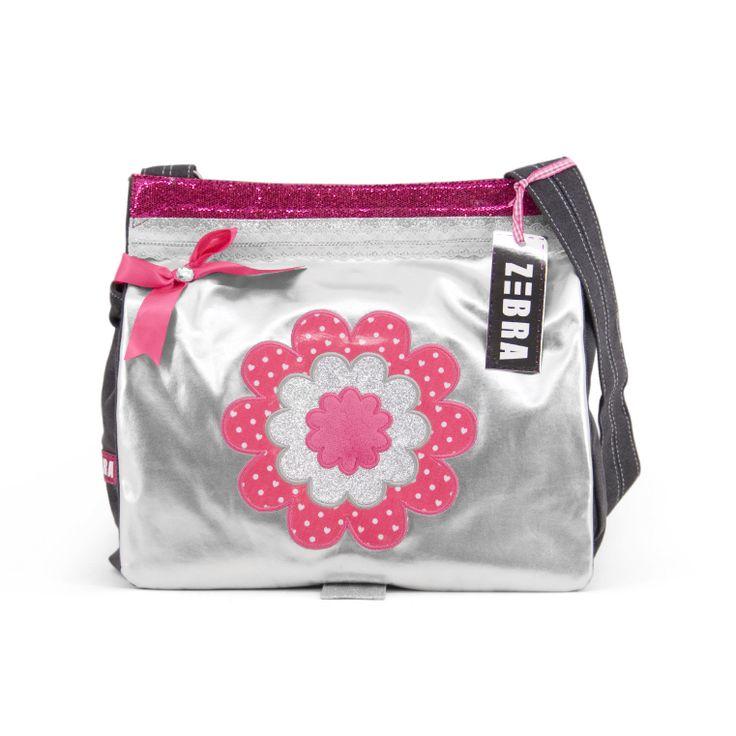 Junior A4 tas – Girly bloem  € 39,95 • Afmetingen: 36 x 33 x 8 cm. De zilveren junior A4 tas heeft een grote bloem en een roze strikje op de voorkant.  De flap van de tas is te sluiten door middel van een drukknoop en de binnenkant van de tas door middel van een rits. De tas bevat twee vakken voor je drinkbeker en een mobielhouder. Daarbij is de tas voorzien van een verstelbare schouderband.