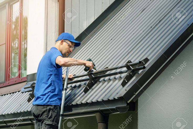 Roofer Installing Snow Guard On Metal Roof Stock Photo Sponsored Paid Snow Guard Roofer Installing Stock In 2020 Roof Installation Foam Roofing Roofing