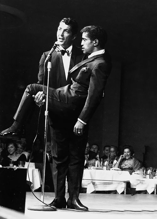 Dean Martin holds up Sammy Davis Jr. on stage at The Sands Hotel and Casino in Las Vegas, 1963.