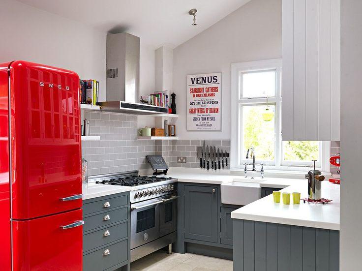 Серый кухонный фартук с имитацией кирпичной кладки, серый гарнитур с белой столешницей, металлический блеск бытовой техники – простой и функциональный дизайн, подчеркивающий яркие всплески. Красный ретро-холодильник – уникальный предмет в кухонном интерьере
