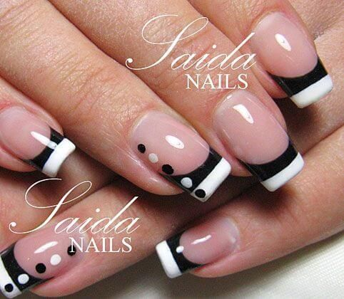 nude nail polish with black and white striped tips and dots on the accent nails