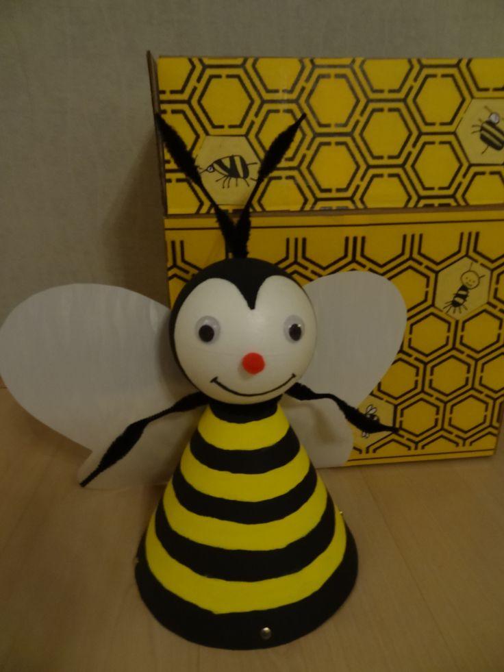 Een Bij gemaakt van papieren puntzak + piepschuim bal. Vleugels van glimmend papier. Doos versierd met honingraat afbeelding.