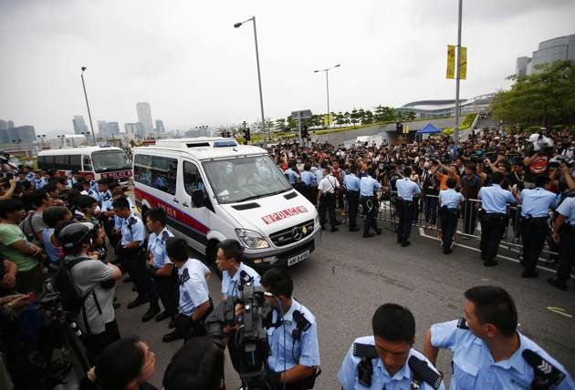 Police vehicles drive into the offices of Hong Kong's Chief Executive Leung Chun-ying
