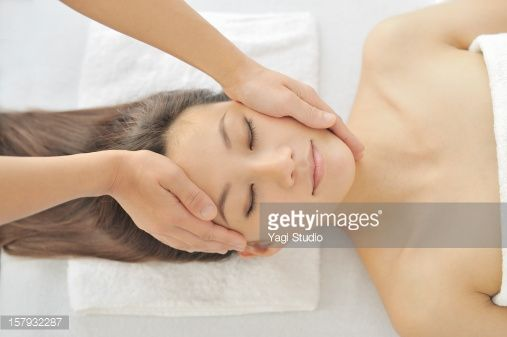 Stock Photo : Young woman receiving face massage, eyes closed