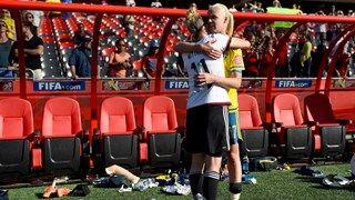 Anja Mittag of Germany hughs Caroline Seger of Sweden