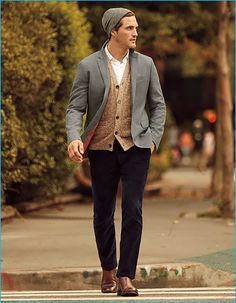 Ollie Edwards layers for fall in Banana Republic's grey sport coat with a white button-down shirt, cardigan sweater, knit beanie, navy corduroy pants, and brown leather boots.