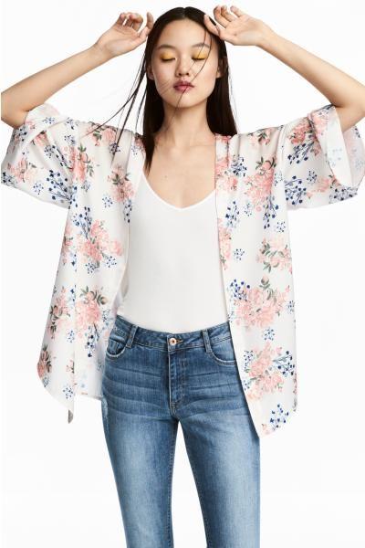 Kimono corto de satén con hombros caídos, mangas holgadas tres cuartos y aberturas laterales. Sin cierre.