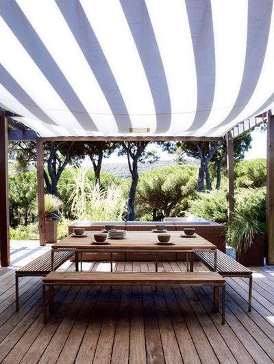 Terrasse toute de bois vêtue, couverte d'un voile rayée.