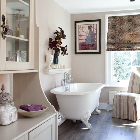 Classic neutral bathroom. This room has a serene feel thanks to the neutral palette, soft brown furnishings, freestanding bath and clutter-free design. Accessories, such as the candles and wall art add character. #bathroom #toilet #shower
