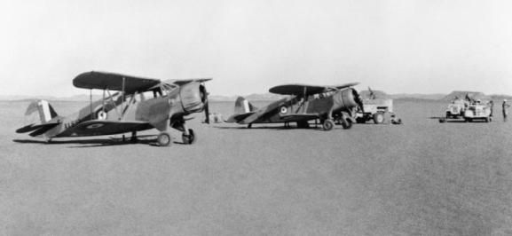 THE LONG RANGE DESERT GROUP (LRDG) DURING THE SECOND WORLD WAR Waco YKC, AX697 (left), and Waco ZGC-7, AX695 (right), of the Long Range Desert Group, on the ground in the Western Desert of Egypt between Kufra and Siwa after landing supplies for 'Y' Patrol. The aircraft were 'acquired' by the LRDG's second-in-command, Major G L Prendergast (a pilot himself) to solve the problem of supplying widely scattered outposts. The Wacos shortened the trip from Kufra to the Nile from ten days to one.