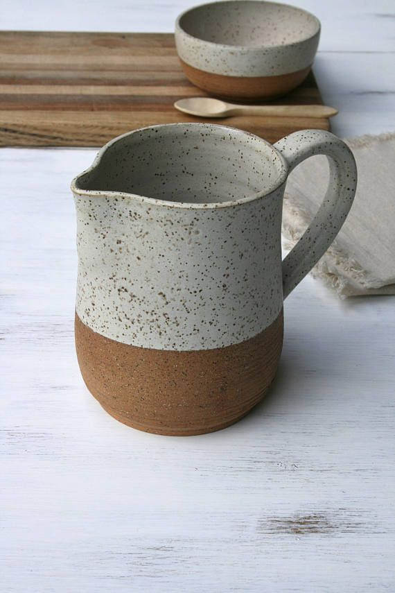 rustic pitcher, speckled stoneware, large jug, rustic pottery, minimal ceramics, matte white, water pitcher, farmhouse, handmade pottery jug Rustic wheel thrown pitcher/jug made from speckled stoneware clay & finished with off-white glaze. This piece is partially unglazed on the lower section to show the beauty of the raw speckled clay body. I added some horizontal textural lines to give the piece a tactile quality & contrast. The handle was hand pulled to fit the jug which gives...