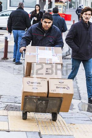 Man is pushing a cart with cardboard boxes