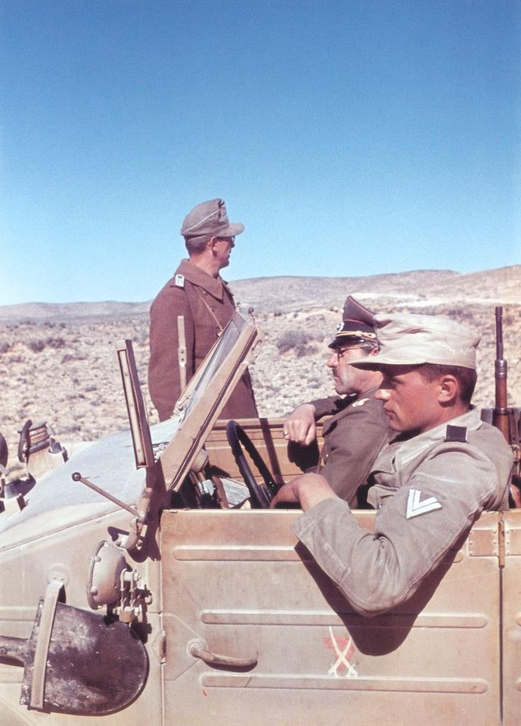 A German Afrika Korps soldier chauffeurs his commander in a Volkswagen Kübelwagen through the deserts of North Africa. 1942.