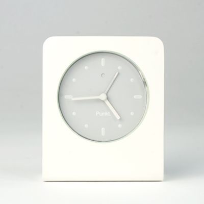 "Punkt Alarm Clock  Offering the simplicity of analog combined with smart details, the clock is made of solid aluminum with a scratch resistant glass face and dial with luminescent hands. A full dial light and the snooze function are activated by pushing the top of the clock. The clock runs on two batteries with one battery devoted exclusively to the light in order to extend the time between battery changes.  3.5""W x 4.25""H  $135.00"