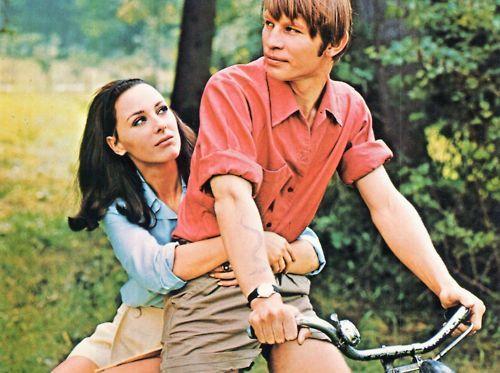 Michael York and Heidelinde Weis ride a bike.