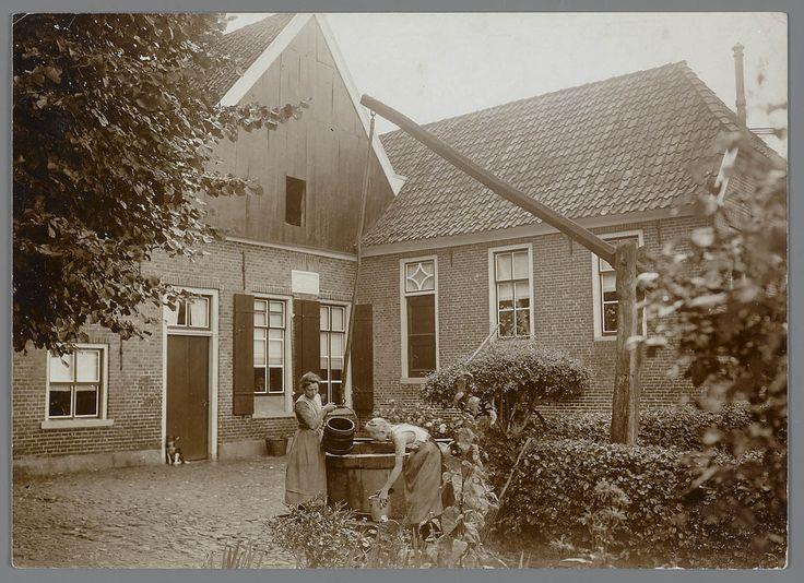 Twee vrouwen in streekdracht bij de waterput van boerderij 't Möllenveld', aan de Hasseltweg te Haaksbergen. de vrouwen dragen hun daagse dracht. In de voorgevel van de boerderij een gevelsteen met het jaartal 1732. #Overijssel #Twente #Saksen