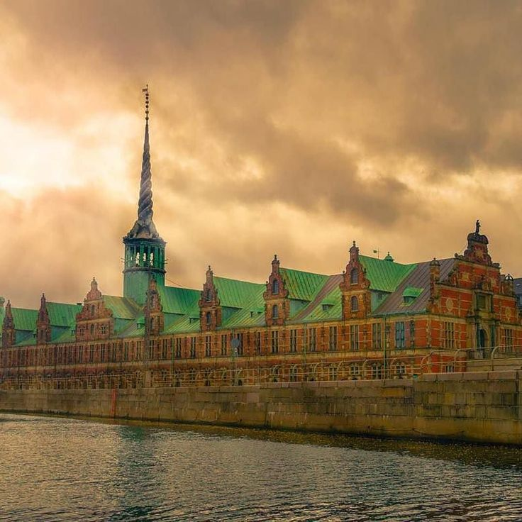 #Repost Photo credit goes to @alexander_lam  The Børsen is a 17th century stock exchange in the centre of Copenhagen. It is often noted for its unique architecture and spires.  With the light piercing through the clouds I just had to stop for a photo. I am a complete sucker for light rays.  One thing that completely surprised me about Copenhagen is the amount of bicycles used for transportation. It seems that the main and preferred mode of transportation in this city are bicycles. So I did…