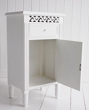 A white bedside cabinet with cupboard and dreawe