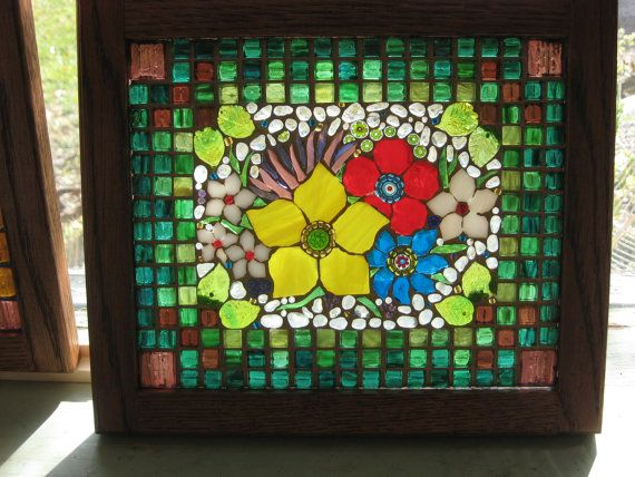 Hand cut stained glass flowers, accents include burgundy Venetian tile, millifiore, clear glass pebbles, beads and green glass leaves all on a sheet of glass. Grout is gilded with a gold wash and sealed. By the Glass Garden Shop