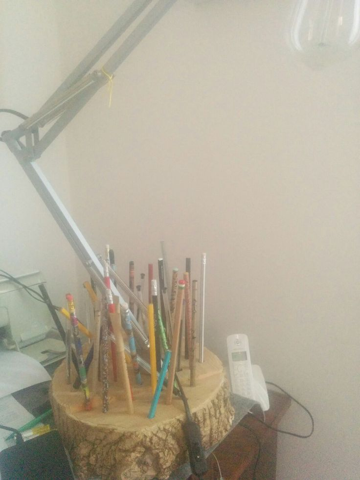 Base per lampada da tavolo e portamatite. Ottenuta da una sezione di tronco di acero sforacchiata a caso col trapano: nel foro centrale è inserita una lampada Ikea, negli altri fori sono inserite matite e penne.