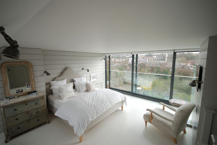 contemporary loft conversion bedroom with full width sliding glass doors