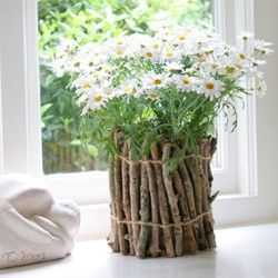 Gather twigs from the yard and wrap around a vase or an empty can and fill with daisies. Love this for a tablescape for spring, especially if using mossy twigs!