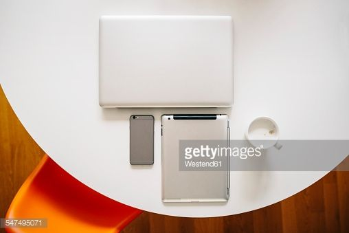 Stock Photo : Three mobile devices and coffee on a white round table