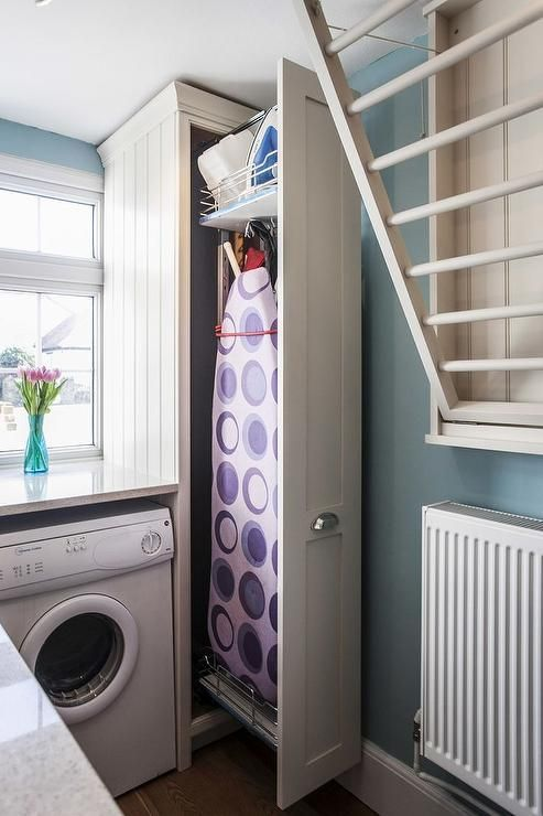 Amazing small laundry room with great storage space. A white front load washer and dryer is tucked under a countertop next to a pull out cabinet filled with an ironing board and iron as well as a pull down drying rack.