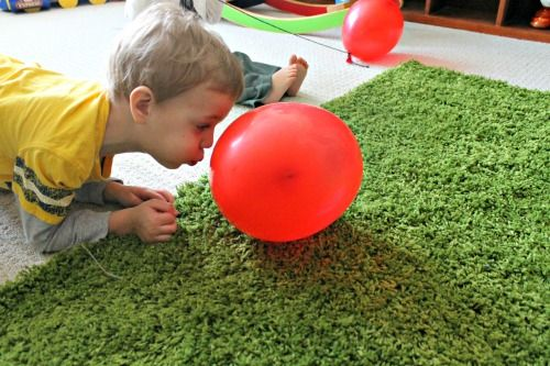Blow the balloon.  Next I wanted to have my little ones crawling and working on those muscles.  We created a simple obstacle course (under a chair, around a pillow) and my little ones got down on their hands and knees and blew the balloon through the obstacle course.