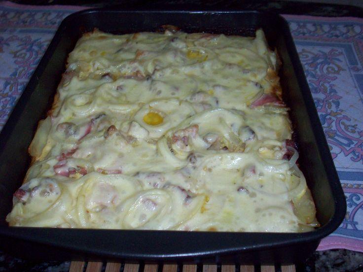 Ingredientes: 5 batatas grandes descascadas e cortadas em rodelas finas , 1 cebola cortada em rodelas , 100 g de presunto picado , 100 g de mussarela picada , 100 g de bacon cortado em cubos pequenos , 1 lata de creme de leite com soro , 1 sache de tempero (sazon) de sua preferência , 2 ovos , 100 g de queijo parmesão ralado , Sal e pimenta a gosto , Manteiga para untar forma. , Azeite para regar. ,