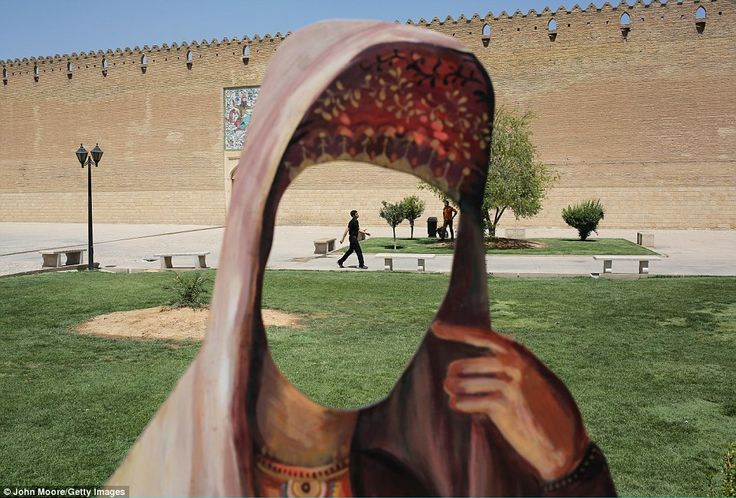 A cut-out of a woman in Iranian dress stands in front of the Karim Khani Palace, a former ...
