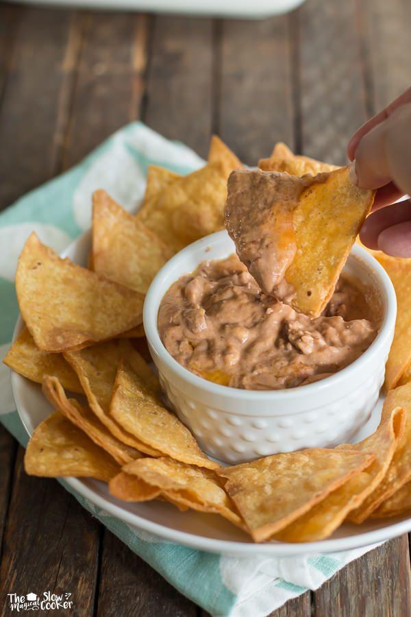 Slow Cooker Creamy Bean and Cheese Dip met 2 blikjes bonen (2 uren). Lekker met warme taco chips uit de oven.