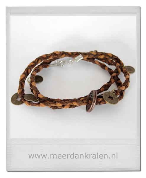 Gevlochten wikkelarmband  Dit is een gevlochten wikkelarmband van 2 suede veters en 1 bruin satijnlint. Het satijnlint geeft een mooie speelse glans aan de armband. Aan de armband hangen op diverse plaatsen bronzen muntjes.