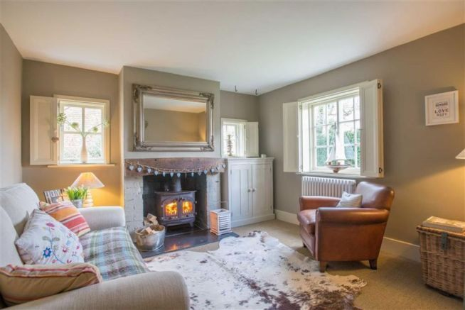 A cosy woodburner takes pride of place in this snug. Attractive double aspect windows and shutters.