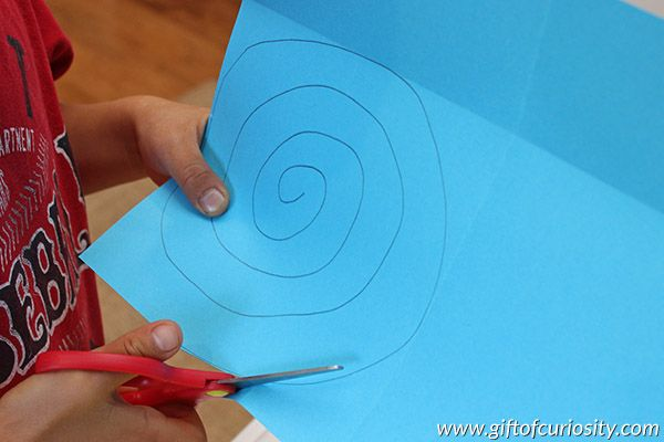 How do hurricanes form? With a spiral cut piece of paper and a lamp, you can model how hot air rises off the ocean to create a hurricane over warm water. This is a great way for kids to learn about extreme weather. || Gift of Curiosity