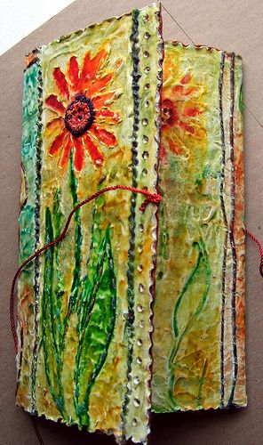 Cover folded by annrowley, via Flickr..made from a class by Frances Pickering. It is done with a thick layer of gesso, drawn onto then dried. Painted, stitched, burnt with a soldering iron and coated with 2 layers of acrylic wax